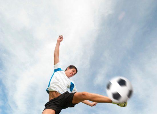 Man jumping to kick a soccer ball