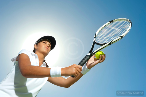 Woman holding a tennis racquet ready for a serve