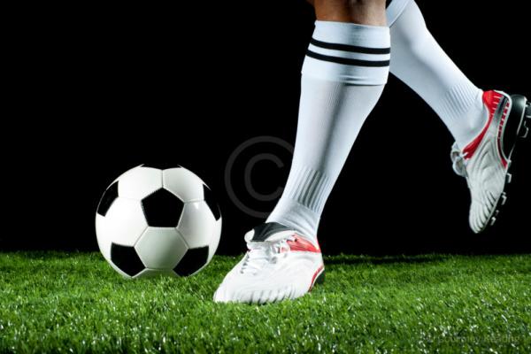 Close up of a man kicking a soccer ball