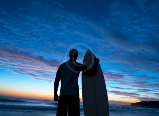 Silhouette of a young man holding a surfboard