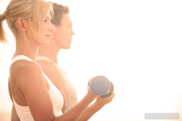Man and woman exercising with weights