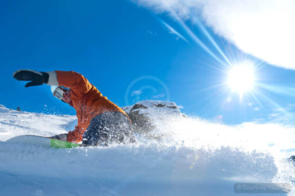 Snowboarder turning on a blue sky day